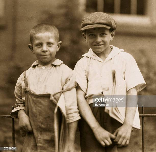 Portrait of a pair of cousins who are two of the youngest newsboys in town as they lean against a fence Hartford Connecticut August 25 1924