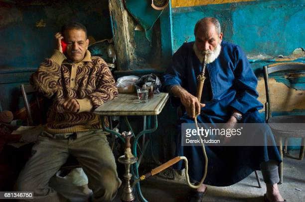 Portrait of a pair of men in an unspecified cafe in the port district Alexandria Egypt December 4 2009 The man at left holds a transistor radio up to...