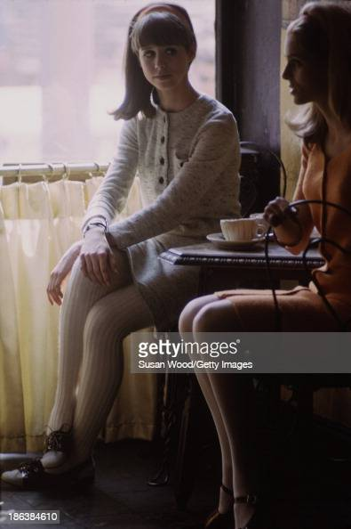 Portrait of a pair of models as they pose in a Soho coffeeshop for a fashion shoot New York New York May 1966 One woman wears a matching cream wool...