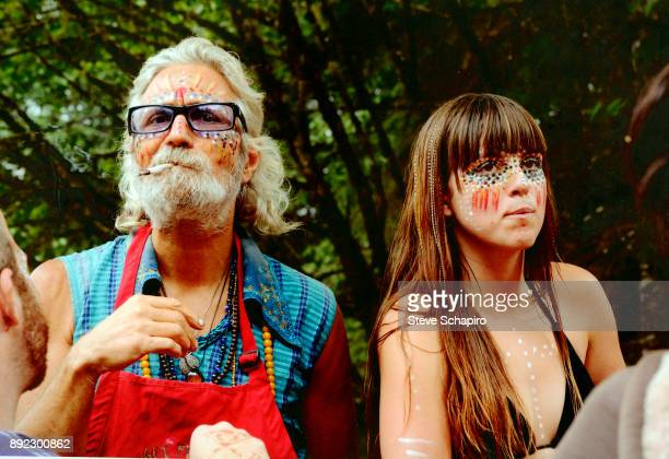 Portrait of a pair of unidentified 'hippies' both with face paint Oregon 2012 The man is dressed in a sleeveless shirt and apron the woman wears a...