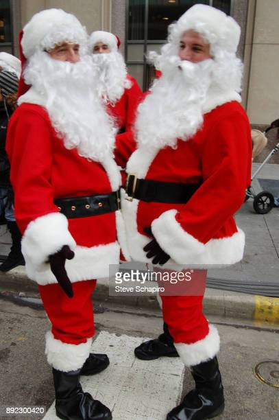 Portrait of a pair of unidentified men both dressed in Santa Claus costumes stand belly to belly on a street Chicago Illinois January 7 2007 A third...