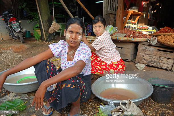 Portrait of a pair of women as they sell fruits and vegetables at an outdoor market Pyay Myanmar 2013 Both wear thanaka paste on their faces a...