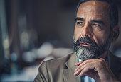 Portrait of a bearded senior man thinking of something.