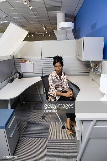 Portrait of a pensive young woman sitting in a new office cubicle