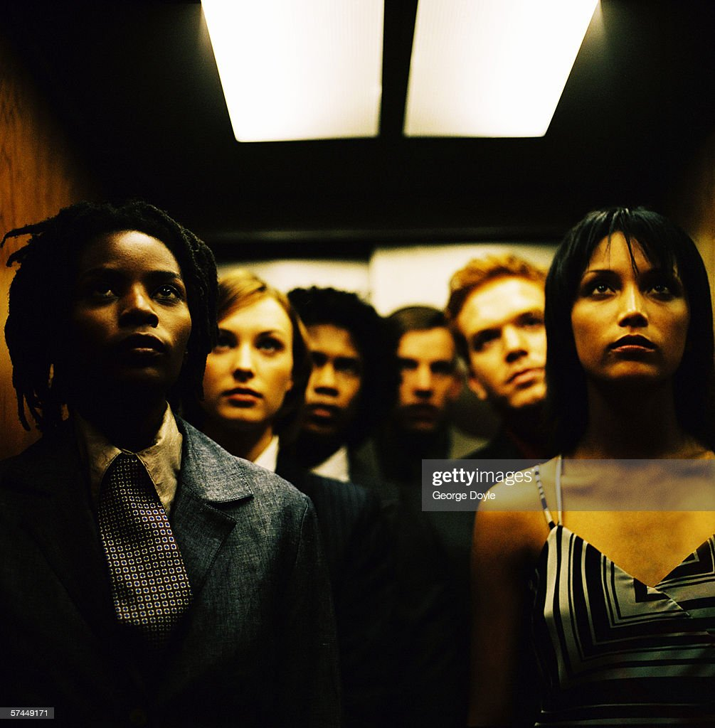 people standing in elevator. portrait of a people standing in dark elevator : stock photo