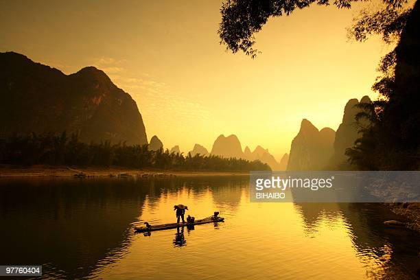 Portrait of a person fishing on a lake at sunset