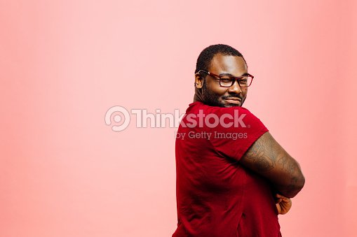 Portrait of a plus size man in red shirt and glasses looking back at camera : Stock Photo