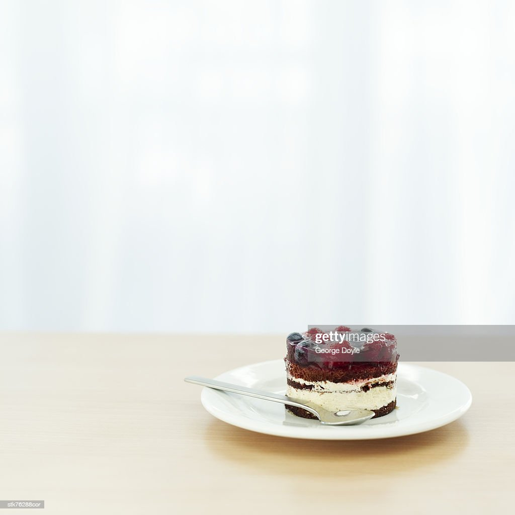 portrait of a portion of dessert on a plate with a dessert spoon : Stock Photo