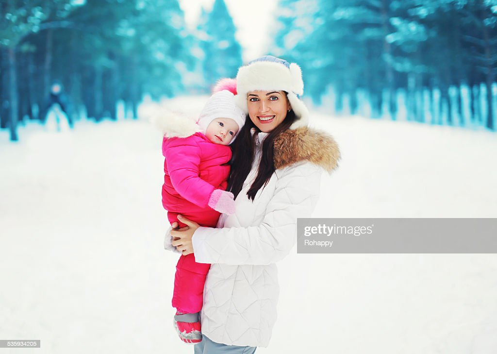 Portrait of a pretty mother and baby in the winter : Stock Photo