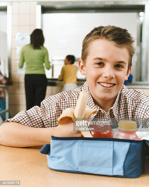 Portrait of a Primary Schoolboy With an Healthy Packed Lunch, Holding a Banana