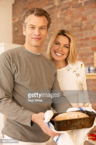 Portrait of a Proud Couple Standing in a Kitchen with the Man Holding a Baking Tray Containing a Freshly Baked Loaf : Stock Photo