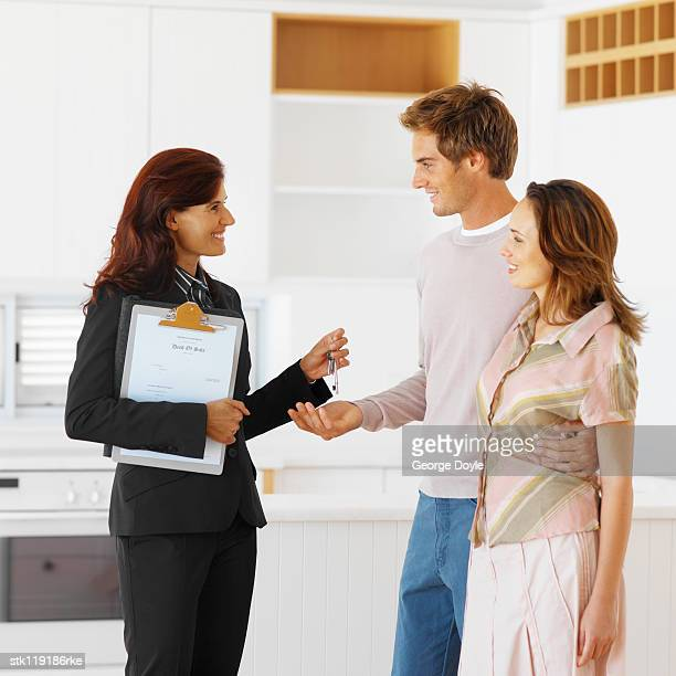 portrait of a real-estate dealer handing over a set of keys to a young couple