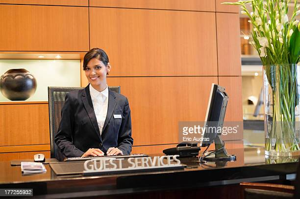 Portrait of a receptionist smiling at the hotel reception counter