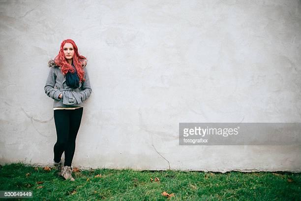 Porträt eines jungen Rotes Haar Frau vor einer Betonwand