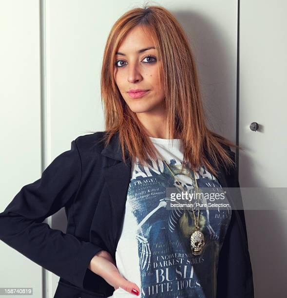 Portrait of a redhead woman agaist a wardrobe.