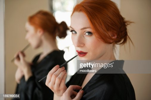 Portrait of a redheaded woman applying lip liner : Stock Photo