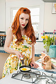 Portrait of a redheaded woman preparing omelet
