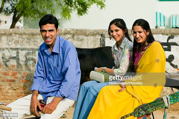 Portrait of a rickshaw driver and two young women sitting in a rickshaw
