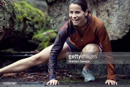 A portrait of a runner stretching in front of old growth trees at Point Defiance. : Stock Photo