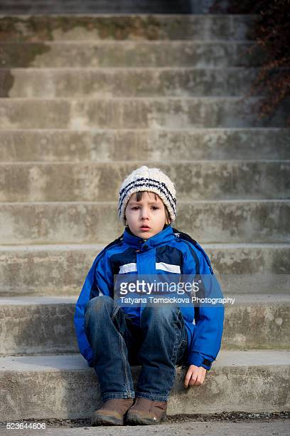 Portrait of a sad boy in the park, sitting on stairs