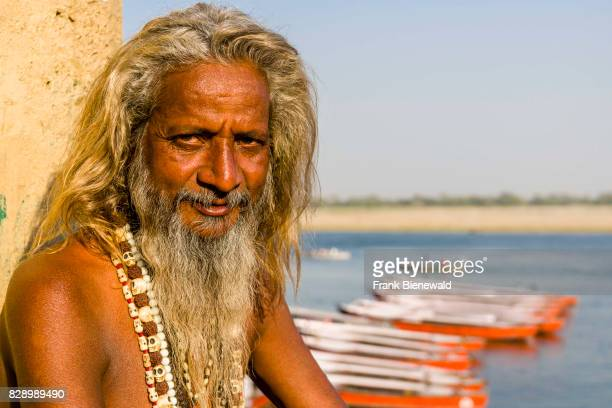 Portrait of a Sadhu holy man sitting on a platform at the holy river Ganges at Dashashwamedh Ghat Main Ghat in the suburb Godowlia