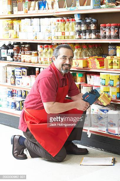 Portrait of a salesman decoding the price of a grocery item with a bar code reader