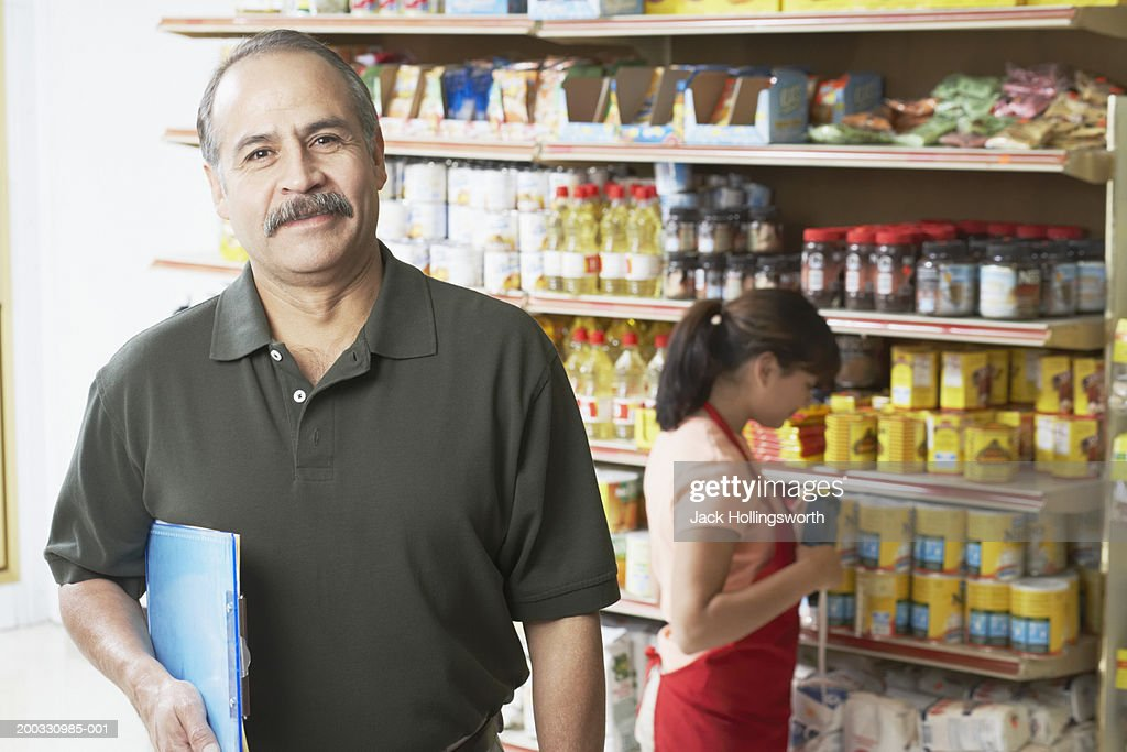 Portrait of a salesman holding a clipboard in a grocery store : Stock Photo