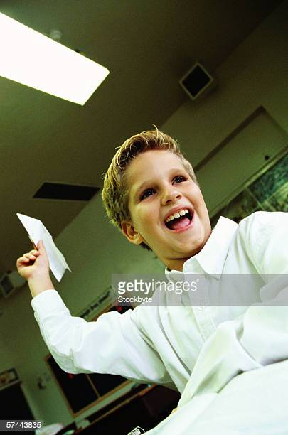 portrait of a school boy (8-10) flying a paper plane in class