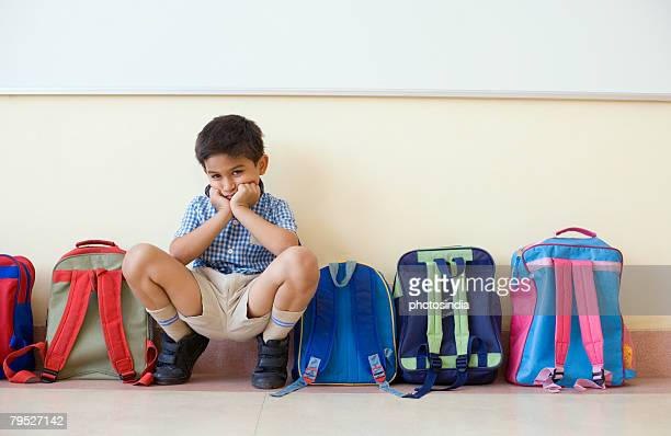 Portrait of a schoolboy crouching near schoolbags and looking sad
