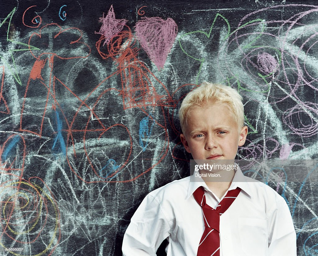 Portrait of a Schoolboy Standing Against a Scribbled Blackboard : Stock Photo
