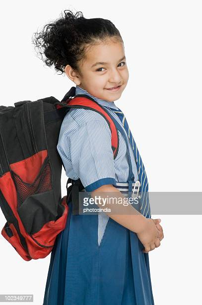 Portrait of a schoolgirl carrying a schoolbag and smiling