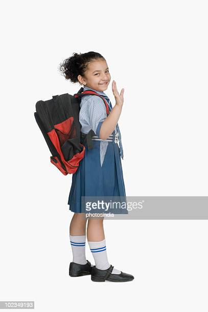 Portrait of a schoolgirl carrying a schoolbag and waving her hand