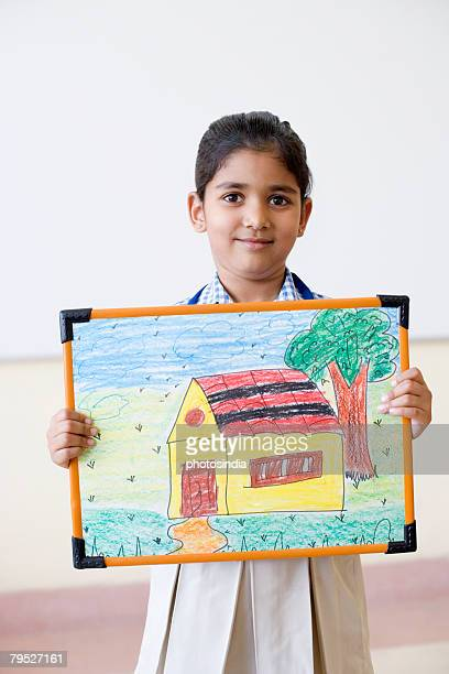 Portrait of a schoolgirl showing a picture frame and smirking