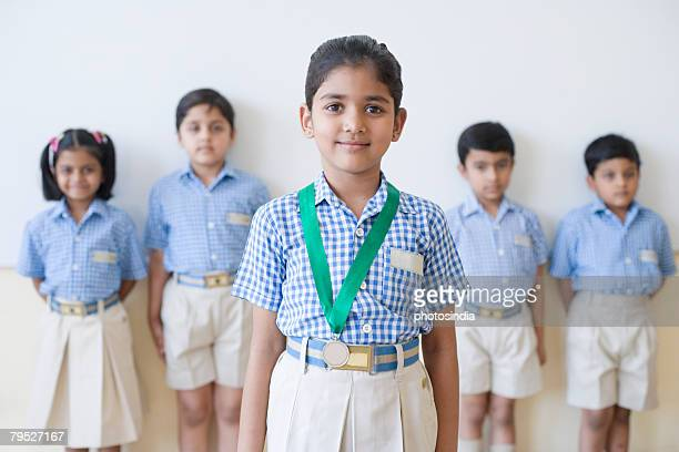Portrait of a schoolgirl with a medal around her neck with her classmates in the background