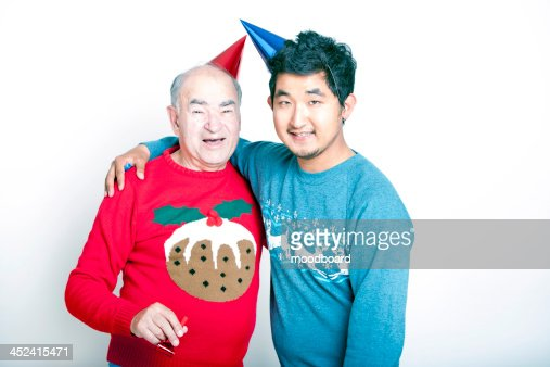 Portrait of a Senior adult man and a young  man wearing Christmas jumpers and party hats : Stock-Foto