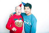 Portrait of a Senior adult man and a young  man wearing Christmas jumpers and party hats