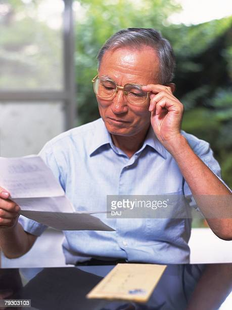 Portrait of a senior adult man reading a letter, High Angle View