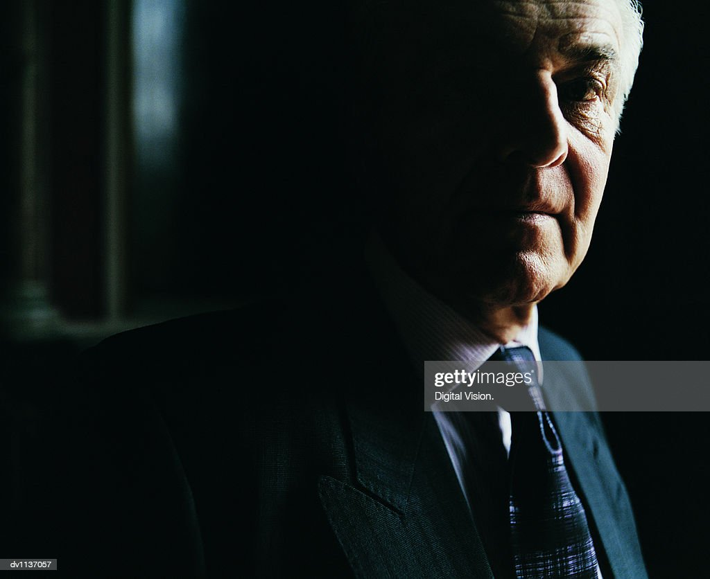 Portrait of a Senior CEO Standing in the Darkness at Home : Stock Photo
