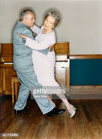 Portrait of a Senior Couple Dancing in a Room with Wooden Flooring and a Piano in the Background : Stock Photo