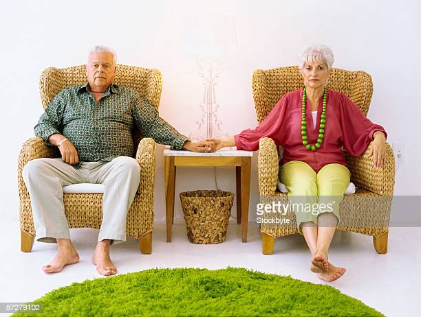 Portrait of a senior couple sitting and holding hands