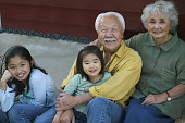 Portrait of a senior couple sitting with their granddaughters