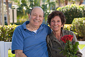 Portrait of a senior couple smiling with a Valentine's rose
