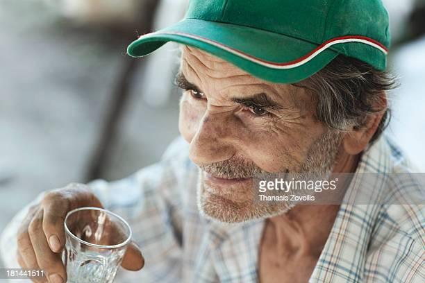 Portrait of a senior man drinking ouzo