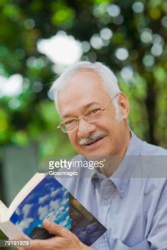 Portrait of a senior man holding a book and smiling : Stock Photo