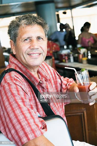 Portrait of a senior man holding a glass of juice and smiling