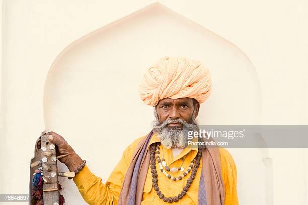 Portrait of a senior man holding a sitar