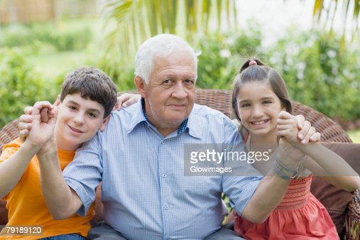 Portrait of a senior man holding his grandchildren's hands and smiling : Foto de stock