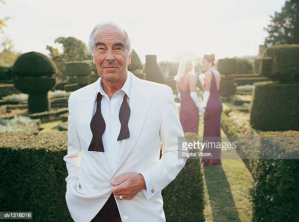 Portrait of a Senior Man in a Formal Garden With Women in the Background
