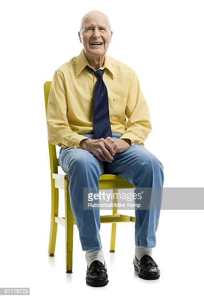 Portrait of a senior man sitting on a chair and smiling