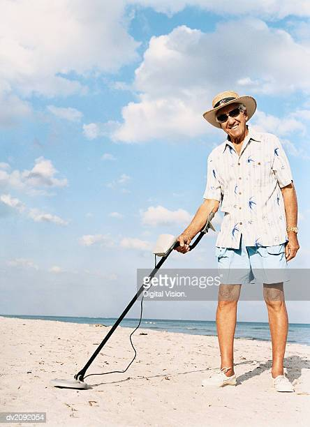 Portrait of a Senior Man Standing on a Beach Holding a Metal Detector